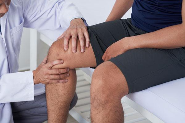 Mann mit Knieschmerzen beim Arzt